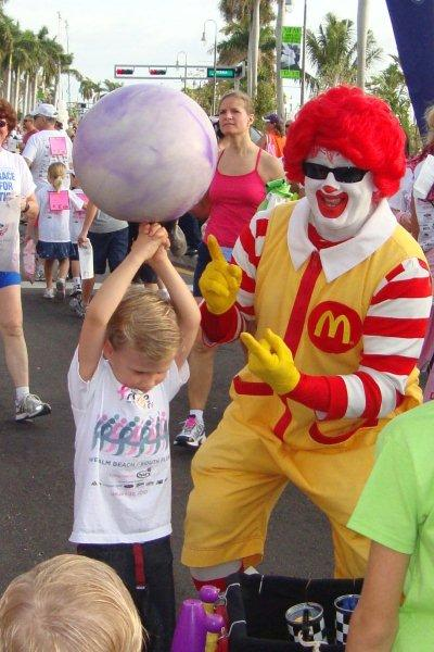 Ronald McDonald helps a young Komen racer with spinning the ball.